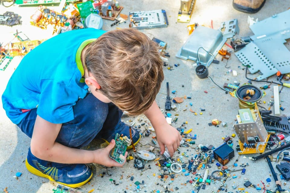 A boy playing with old electronic components