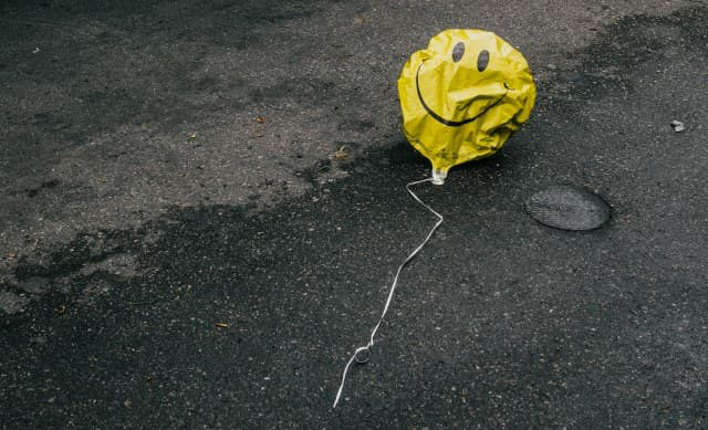 A deflated balloon with a smily face